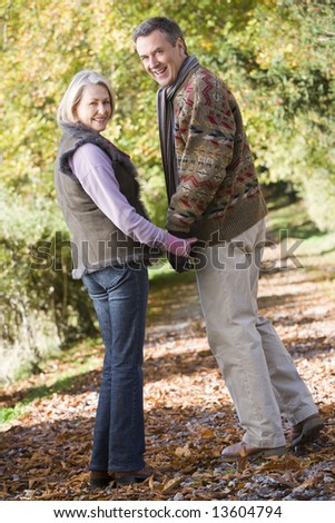 Senior couple on woodland walk through autumn woods