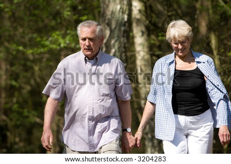 Senior couple out on a summer day strolling through the wood - stock photo