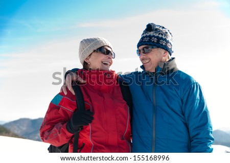 Senior couple outdoor portrait- happy mature man and woman in winter snowy landscape - stock photo