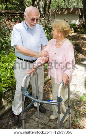 Senior couple outdoors.  She's in a walker and he's helping her. - stock photo
