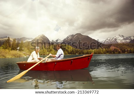 Senior couple paddling on boat on mountain tarn - stock photo