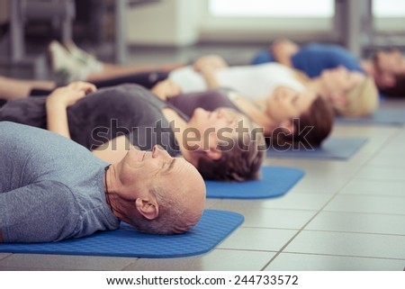 Senior couple participating in aerobics class at the gym with diverse people lying in a receding row on mats, focus to the couple in the foreground, healthy lifestyle concept - stock photo