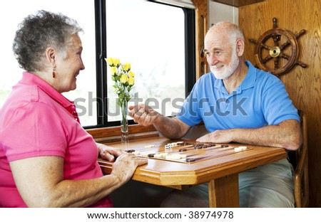 Senior couple playing backgammon in the kitchen of their motor home. - stock photo