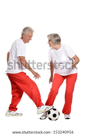 Senior couple playing football in a gym - stock photo