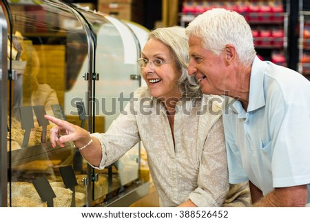 Senior couple pointing puddings at the bakery store - stock photo