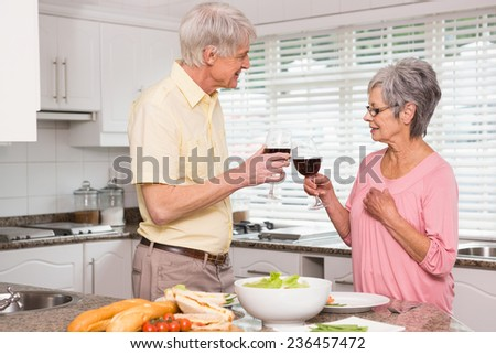 Senior couple preparing lunch together having red wine at home in the kitchen - stock photo