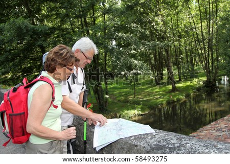 Senior couple rambling by a river, standing on a bridge