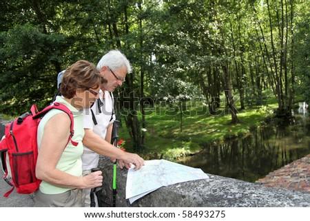 Senior couple rambling by a river, standing on a bridge - stock photo
