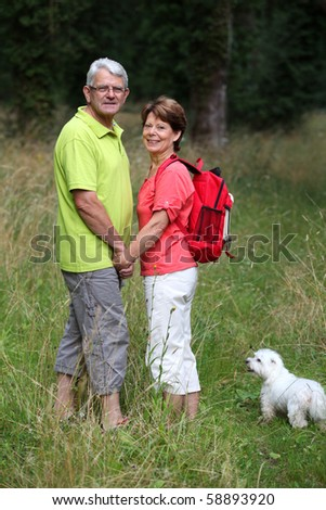 Senior couple rambling in countryside hand in hand - stock photo