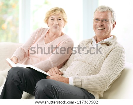 Senior Couple reading a book together at home - stock photo
