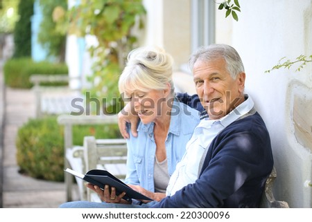 Senior couple reading book outside their house - stock photo