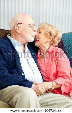 Senior couple relaxing at home, she's laughing as he kisses her nose. - stock photo