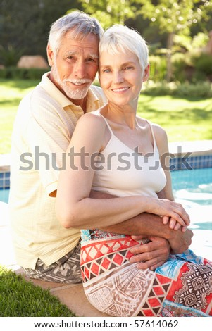 Senior Couple Relaxing By Pool In Garden - stock photo