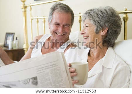 Senior couple relaxing in bed - stock photo
