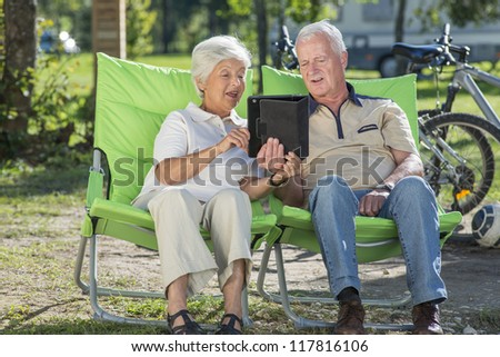 Senior couple relaxing in camp, having fun using their tablet PC - stock photo