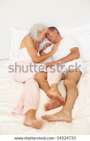 Senior Couple Relaxing On Bed - stock photo