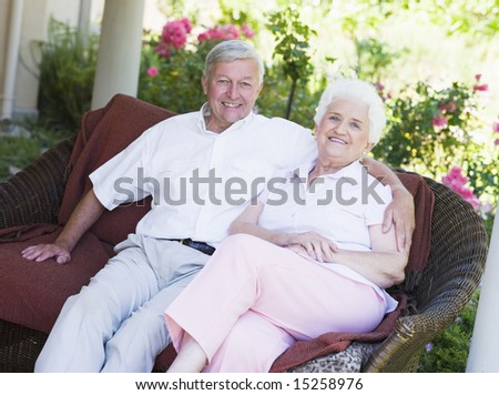 Senior couple relaxing on garden seat looking to  camera - stock photo
