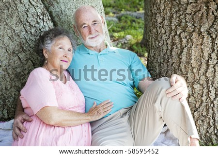 Senior couple relaxing together in the park under a tree. - stock photo