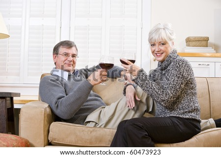 Senior couple relaxing together on couch with glass of red wine - stock photo