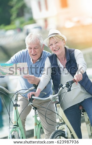 Senior couple riding bikes and reading map in tourist area