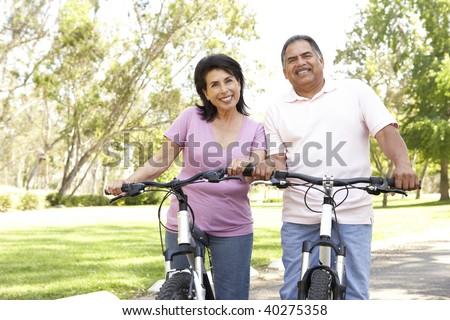 Senior Couple Riding Bikes In Park - stock photo