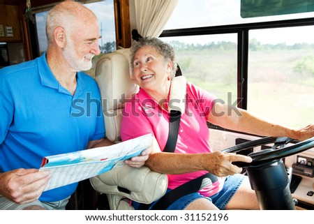 Senior couple riding in their motor home consult a map. - stock photo
