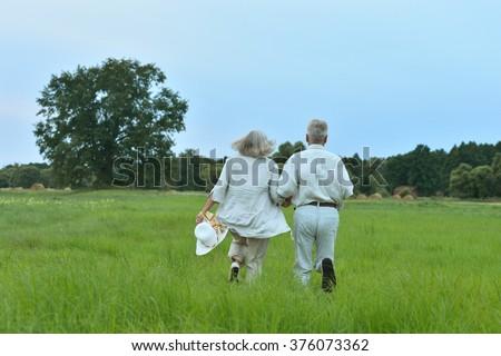 Senior couple running at   field - stock photo