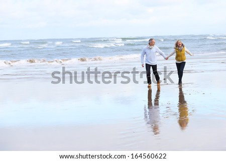 Senior couple running on the beach in winter time - stock photo