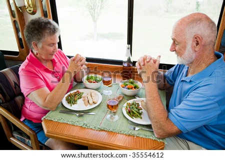 Senior couple say grace before eating a meal in their motor home. - stock photo