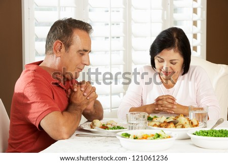 Senior Couple Saying Grace Before Meal At Home - stock photo