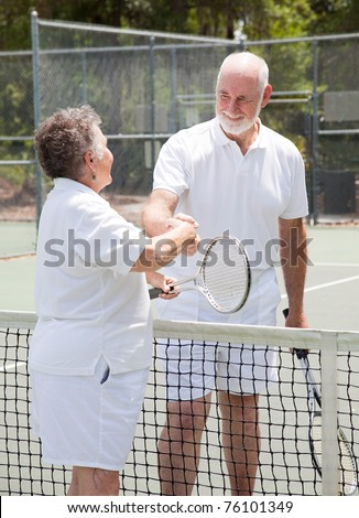 Senior couple shakes hands over the net on the tennis court. - stock photo