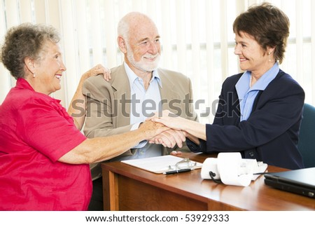Senior couple shakes hands with their financial advisor or broker. - stock photo