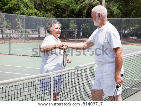 Senior couple shaking hands after their tennis game. - stock photo