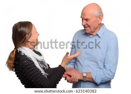 Senior couple sharing a laugh. Old people looking at each other and sharing jokes. Happy moment captured on white background.