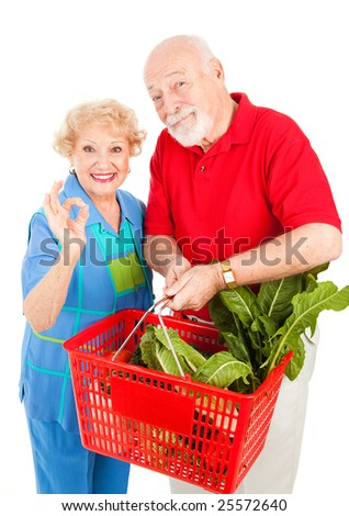 Senior couple shopping for organic produce and giving the okay sign.  Isolated on white.