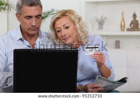 senior couple shopping on the Internet - stock photo