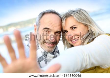 Senior couple showing hands towards camera - stock photo