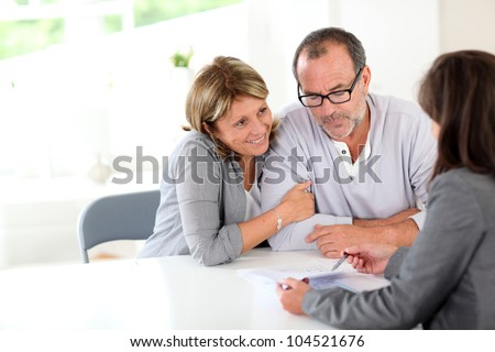 Senior couple signing financial contract - stock photo