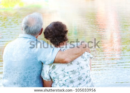 Senior couple sit embracing and looking at water - stock photo