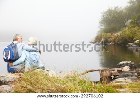 Senior couple sit embracing by a lake, back view - stock photo