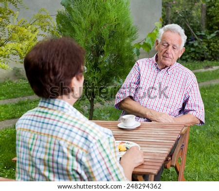 Senior couple sitting in courtyard and having coffee - stock photo