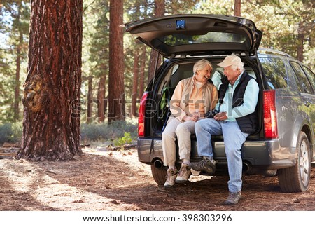 Senior couple sitting in open car trunk preparing for a hike - stock photo