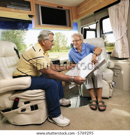 Senior couple sitting in RV looking at map and smiling. - stock photo