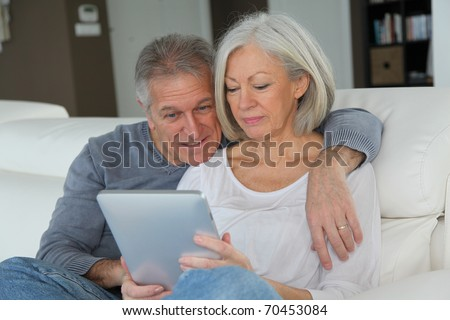 Senior couple sitting in sofa with electronic tablet