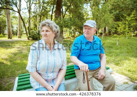 Senior couple sitting on a park bench with walking stick. Elderly couple relaxing outdoors on a summer day.  - stock photo