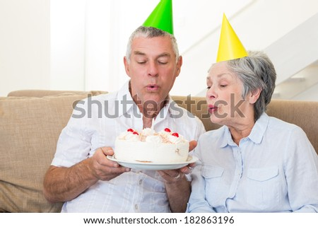 Senior couple sitting on couch celebrating a birthday at home in living room - stock photo