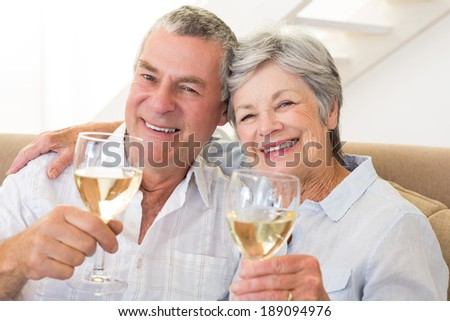 Senior couple sitting on couch having white wine at home in living room - stock photo