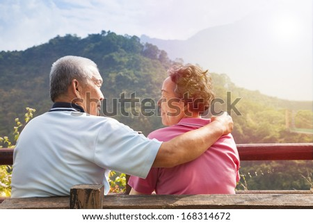 senior couple sitting on the bench in nature park - stock photo