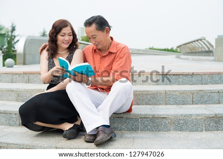 Senior couple sitting outdoors and reading - stock photo