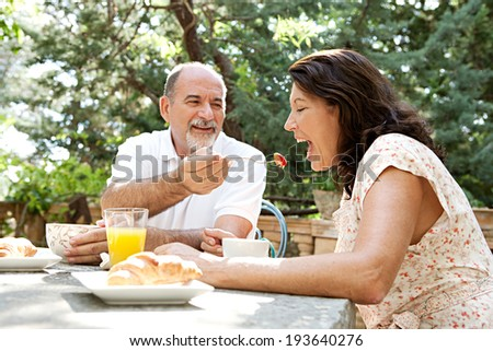 Senior couple sitting together having breakfast in a luxury garden on holiday with the husband feeding the wife a strawberry. Mature people eating and drinking healthy food. Outdoors lifestyle.